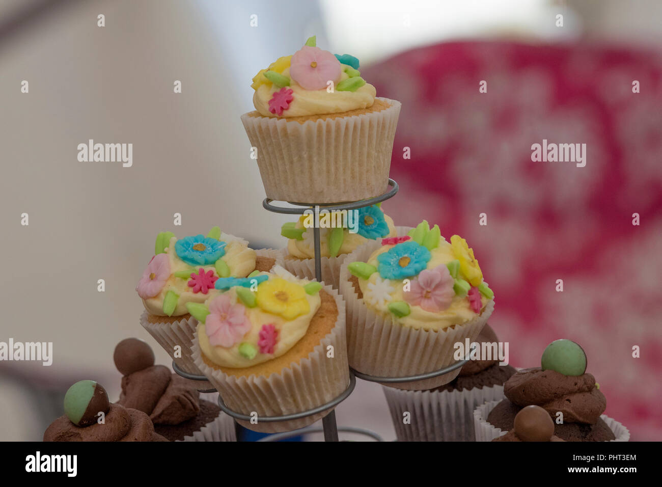 brightly coloured cup cakes decorated on a cake stand Stock Photo