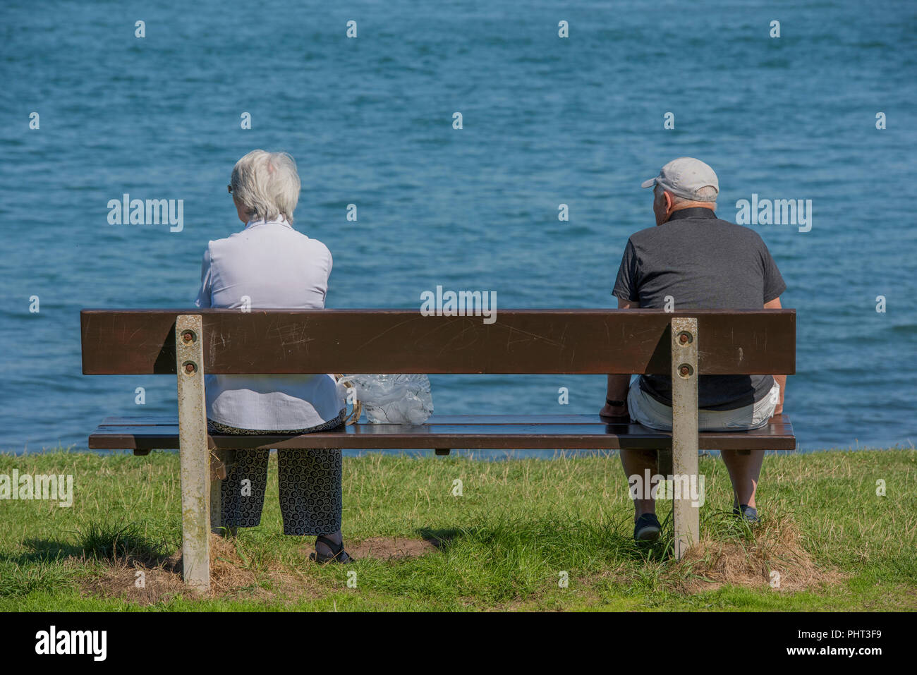 an elderly couple sitting either end of a park bench at the seaside on the isle of wight. retirement and holidays resting and taking it easy. - Stock Image