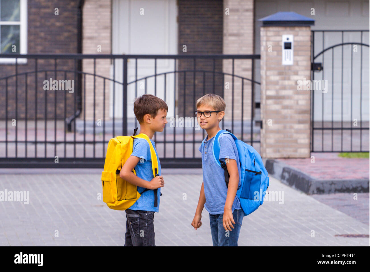 Education, school, friendship concept - two boys with backpacks talking after school outdoors Stock Photo