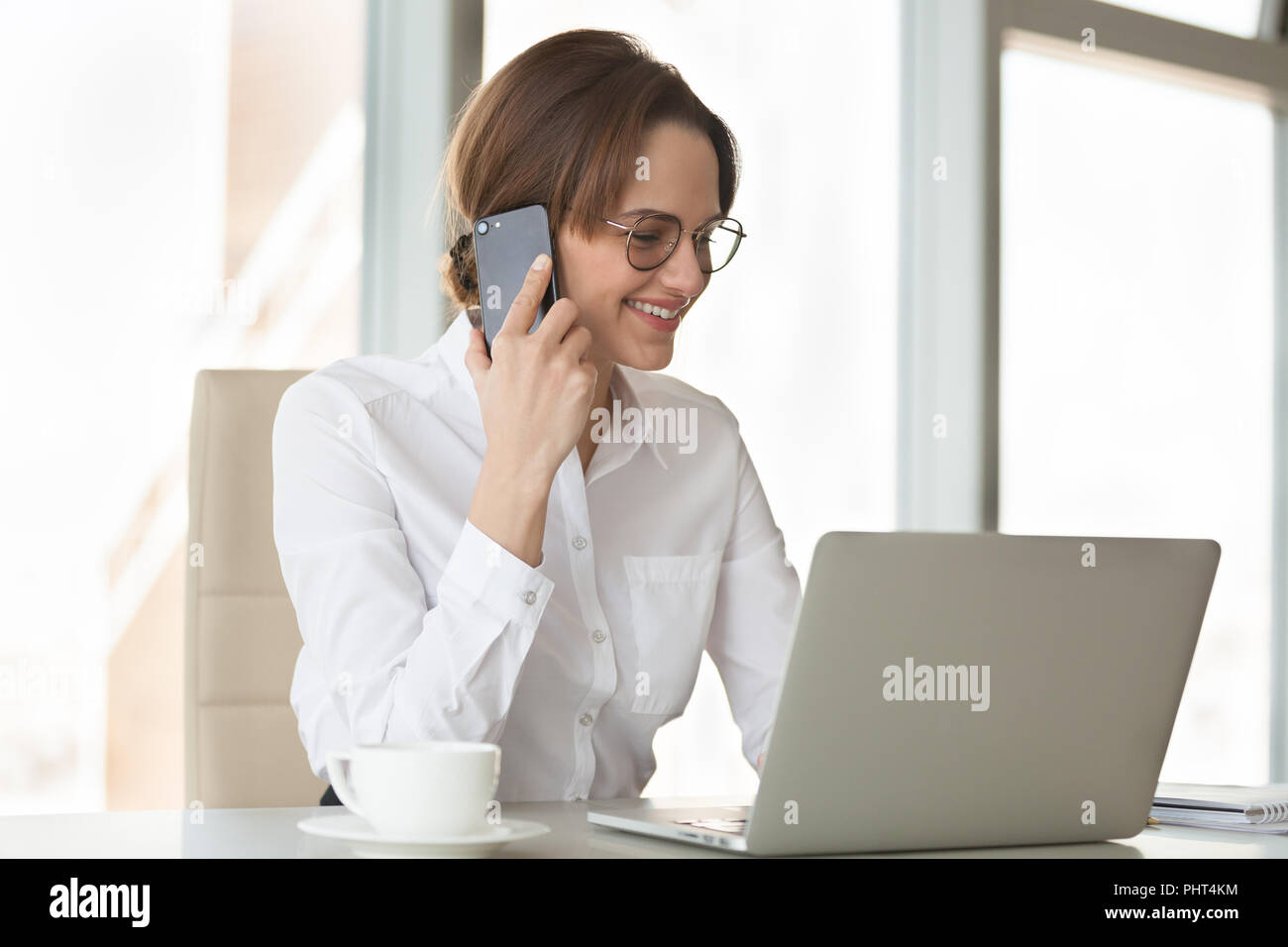 Smiling confident businesswoman making phone call using laptop i - Stock Image
