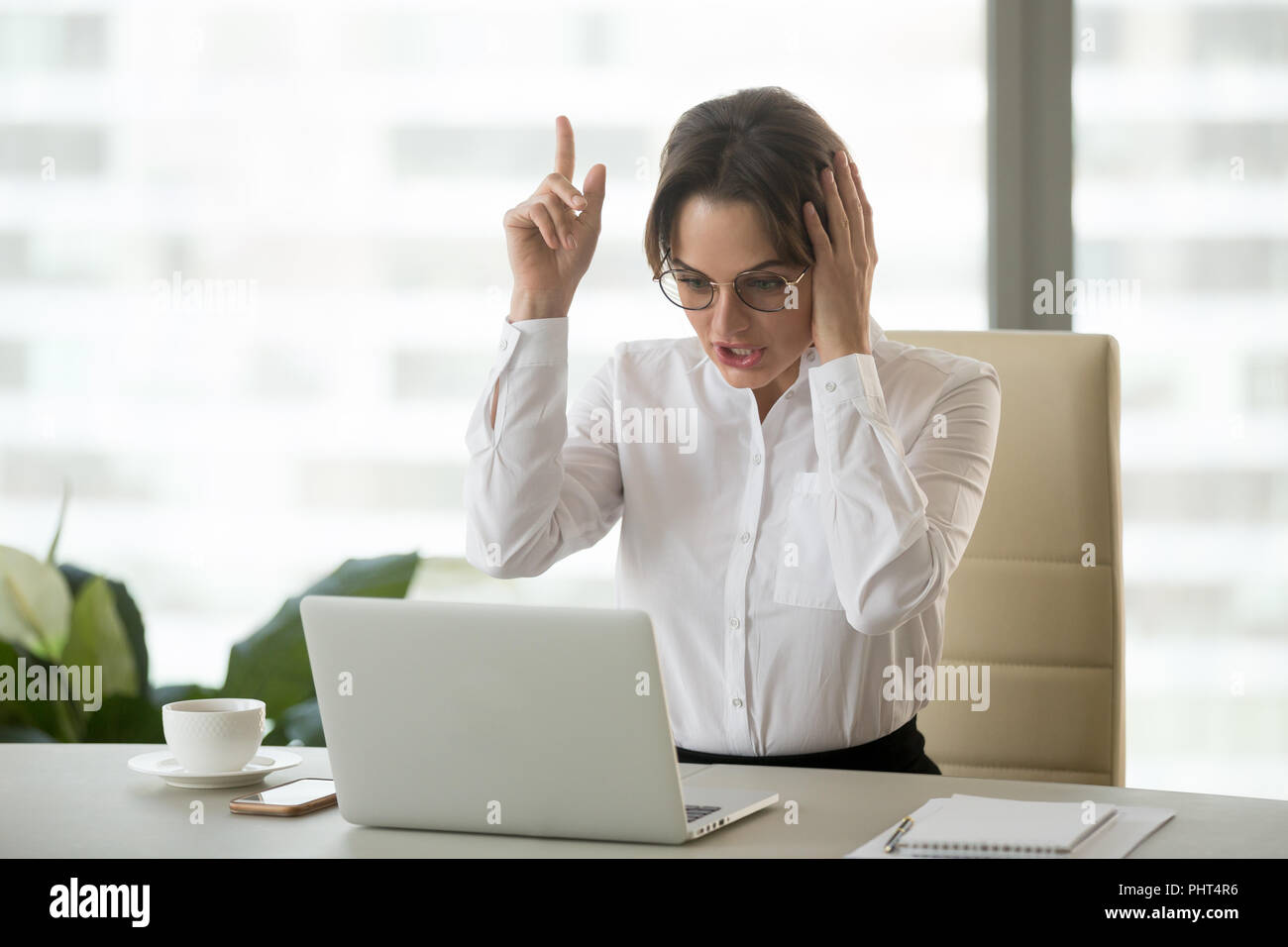 Excited businesswoman got new idea or business solution at work - Stock Image