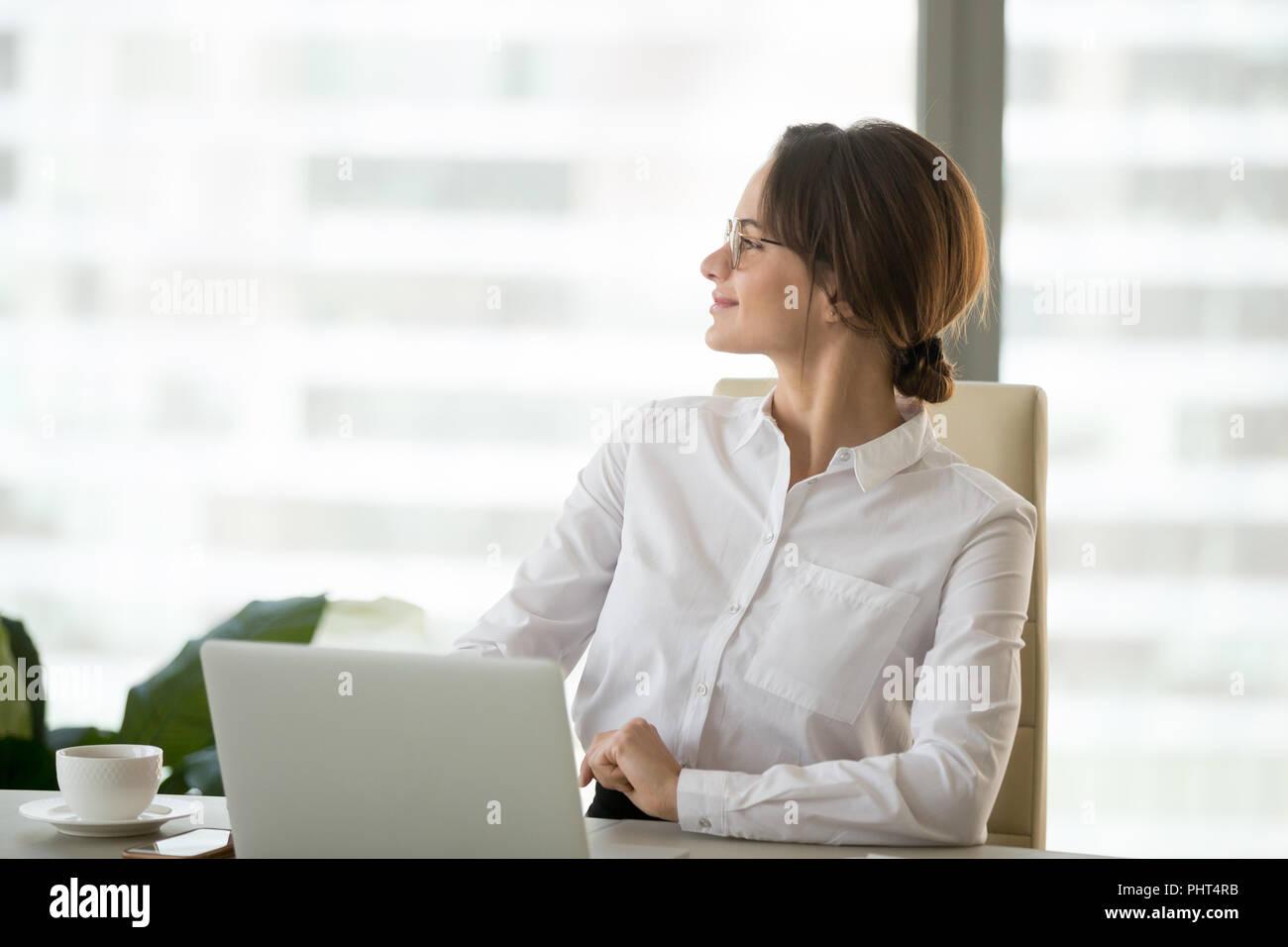 Happy satisfied businesswoman enjoying business success thinking - Stock Image