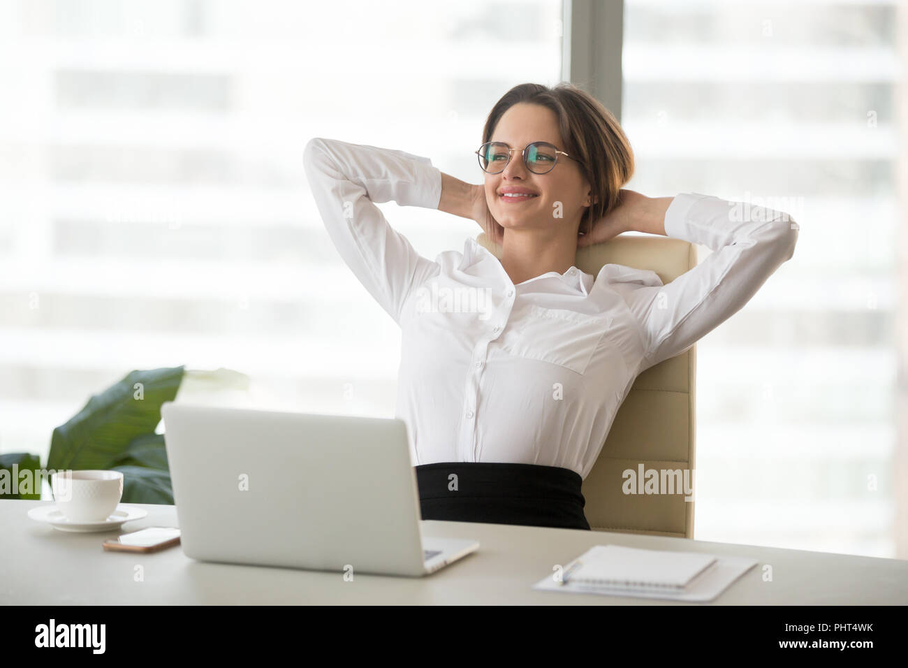 Smiling relaxed businesswoman resting leaning on comfortable erg - Stock Image