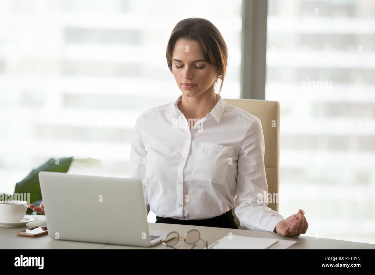 Mindful millennial woman meditating in office to reduce work str - Stock Image