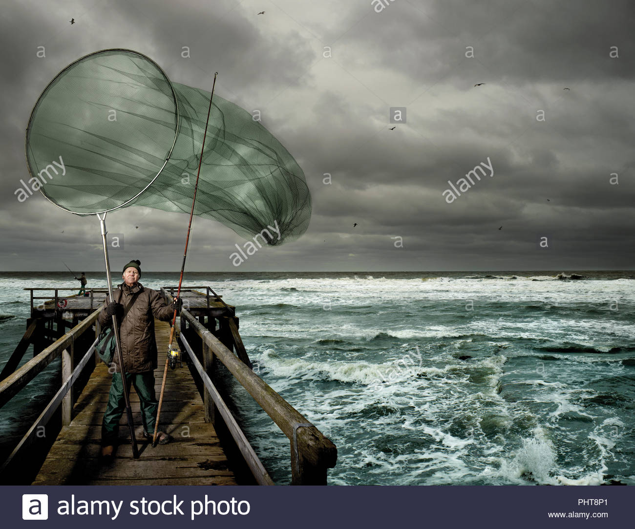 Mautre man on pier with oversized net - Stock Image