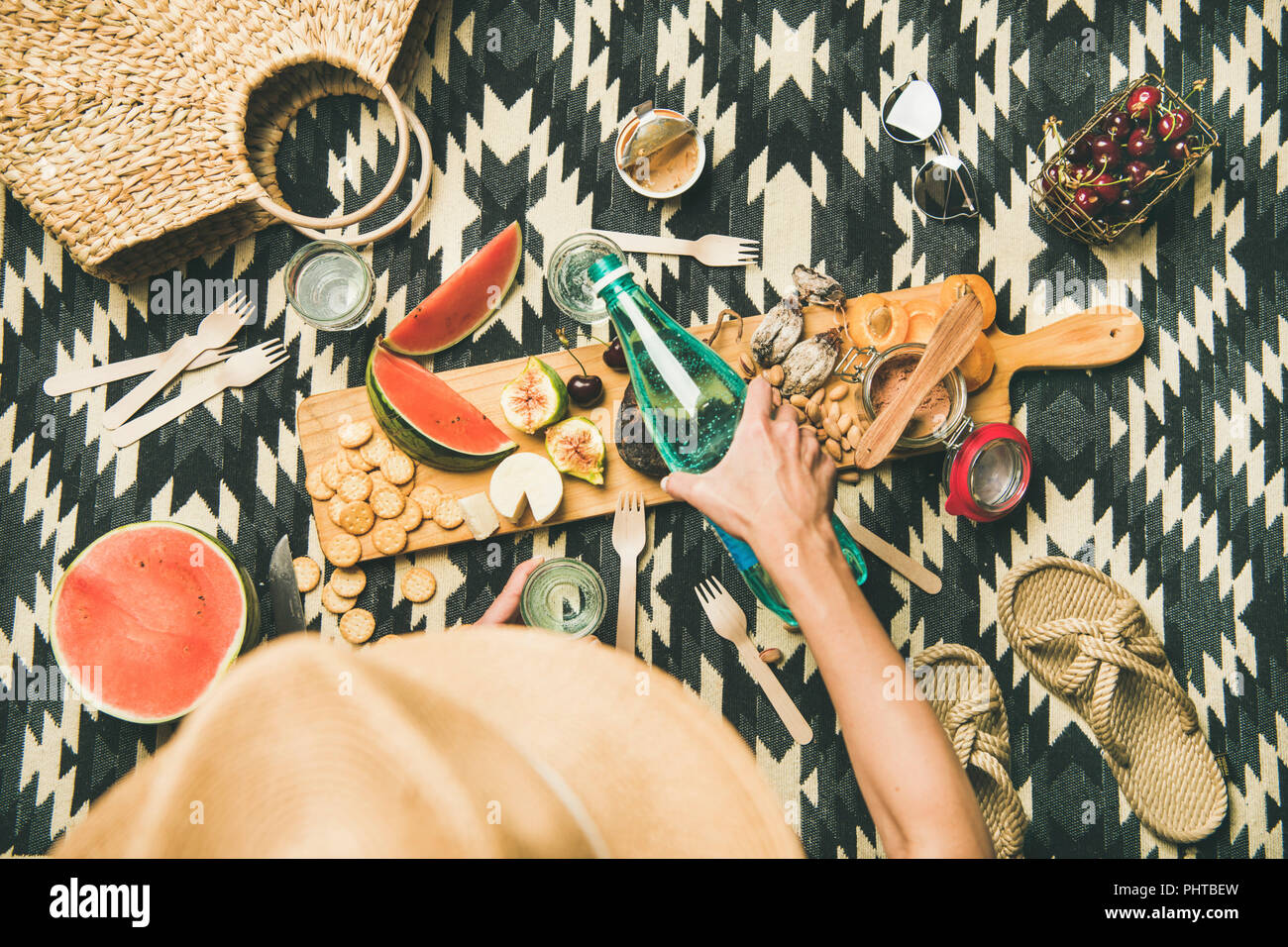 Summer beach picnic setting. Flat-lay of charcuterie board with snacks, watermelon, cherries, beach feminine accesories over picnic blanket, top view, - Stock Image
