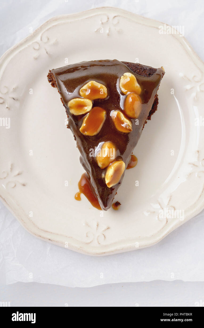 A piece of brownie cake with salted caramel and roasted peanuts Stock Photo