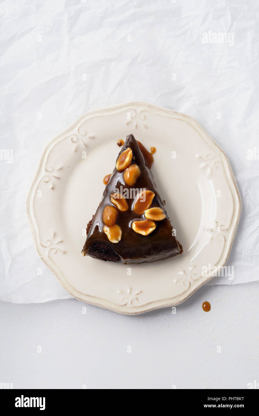 A piece of brownie cake with salted caramel and roasted peanuts - Stock Image