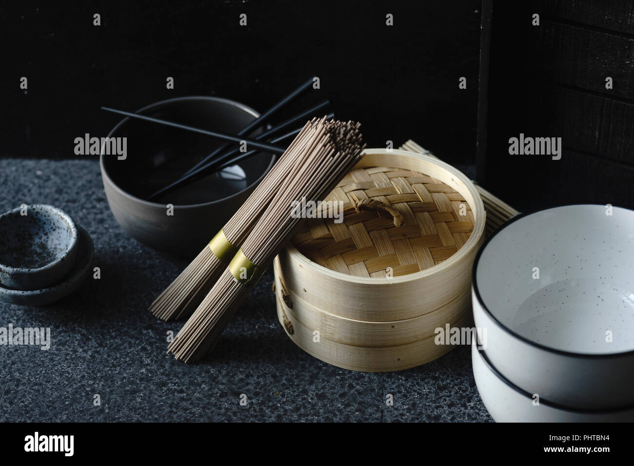 Soba noodles, bamboo steamer and asian cuisine props on dark background - Stock Image