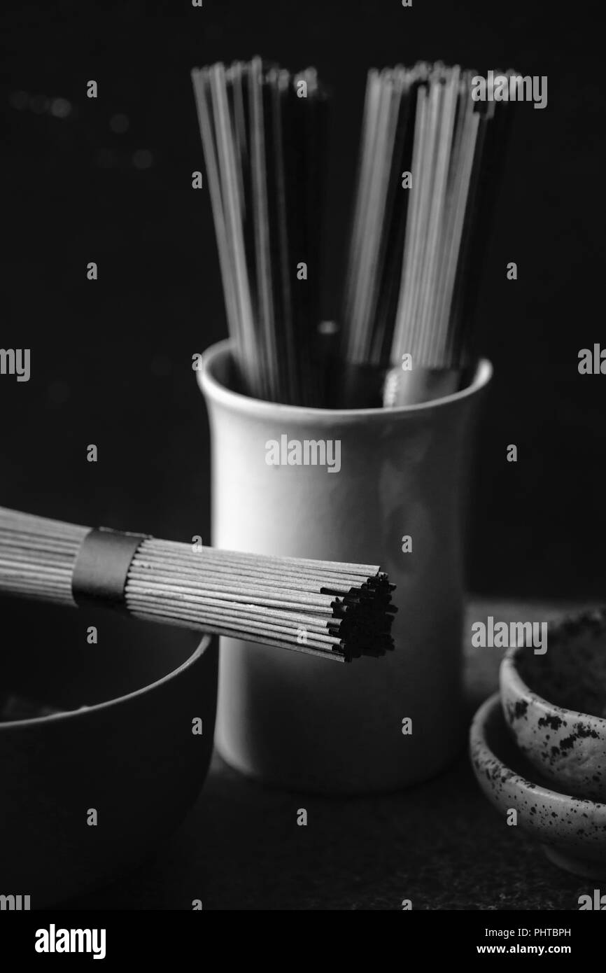 Soba noodles, bamboo steamer and asian cuisine props on dark background. Black and white image - Stock Image
