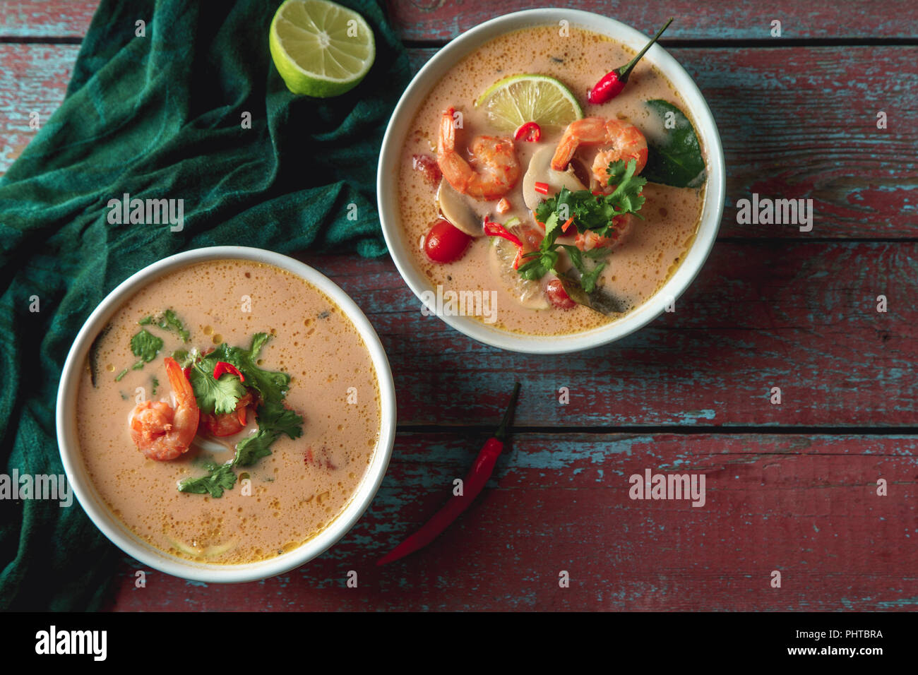 Traditional thai soup tom yum with shrimps and mushrooms, served with fresh lime slices. Top view, rustic wooden background - Stock Image