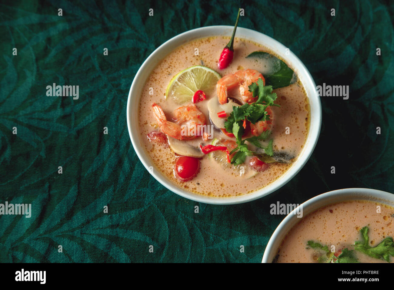 Traditional thai soup tom yum with shrimps and mushrooms, served with fresh lime slices. - Stock Image