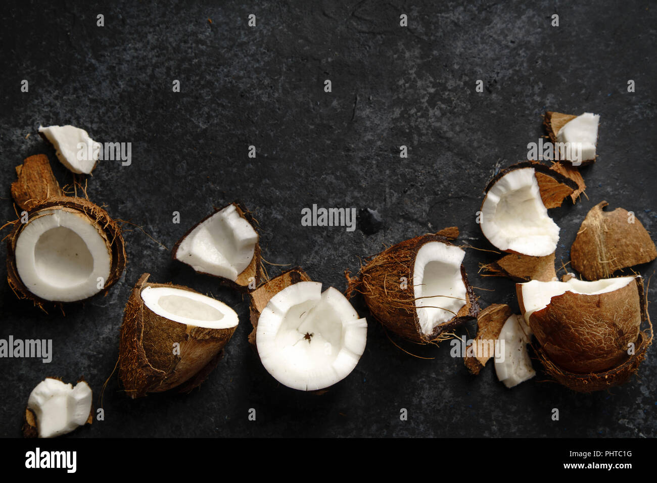 Cracked coconut arranged on dark textured background. Horizontal image with copy space. Soft light. - Stock Image