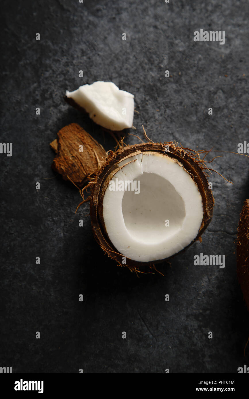Close up image of cracked coconut on dark textured background. Soft light. - Stock Image
