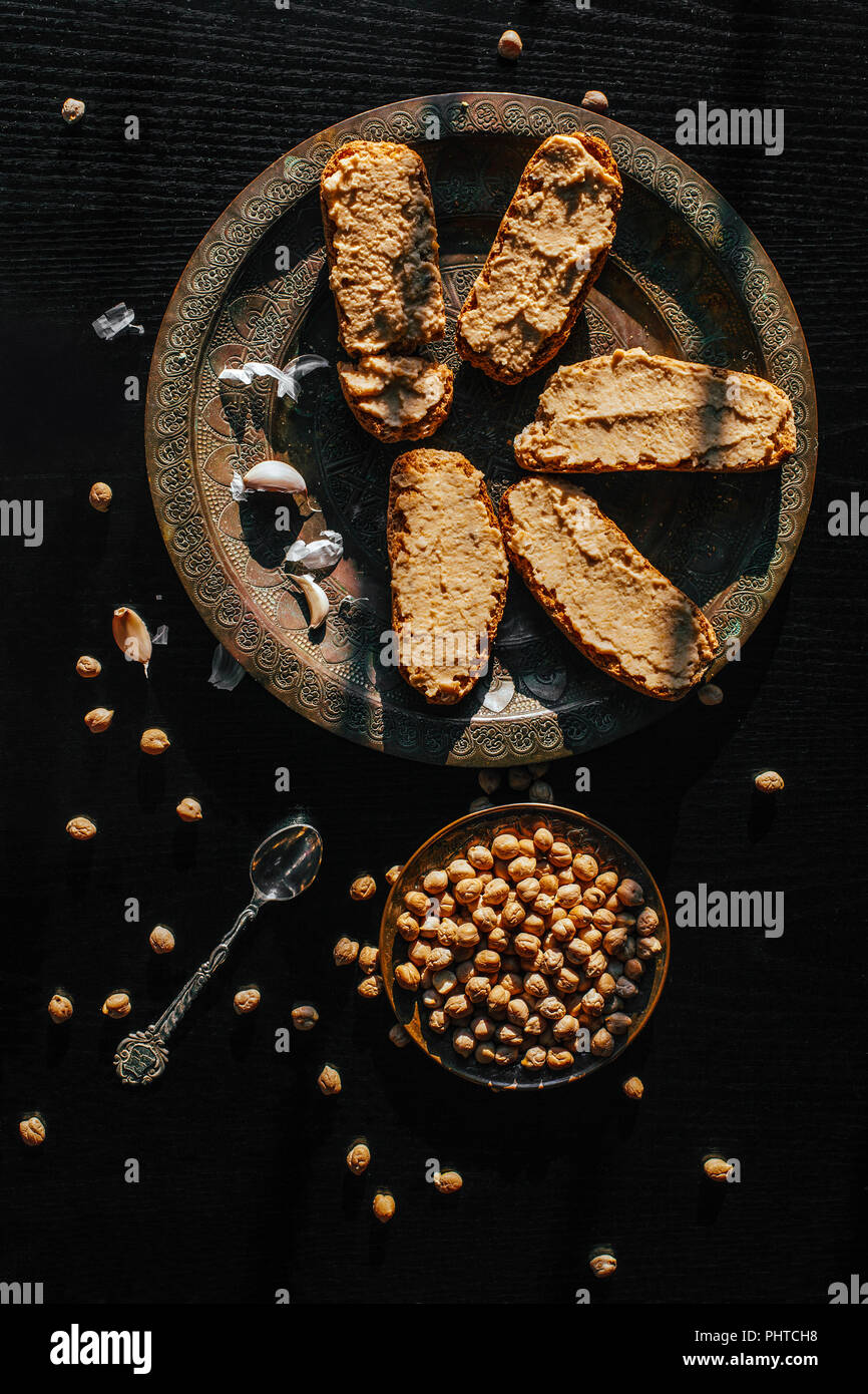 Homemade hummus on a black background - Stock Image