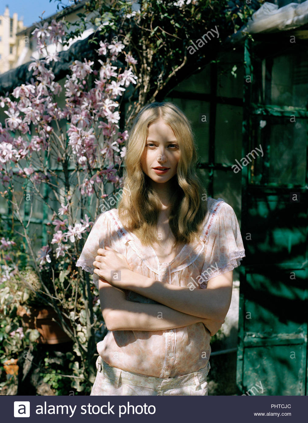 Blond haired young woman in garden - Stock Image