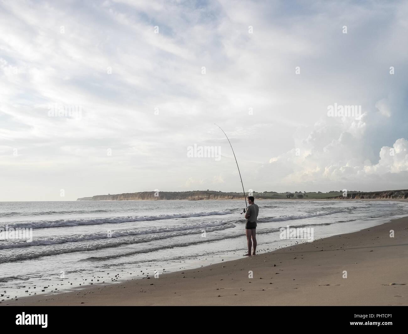 Luanda, Angola - April 26, 2014: Recreational young fisherman standing at beach north of Luanda angling, Angola, Africa. - Stock Image