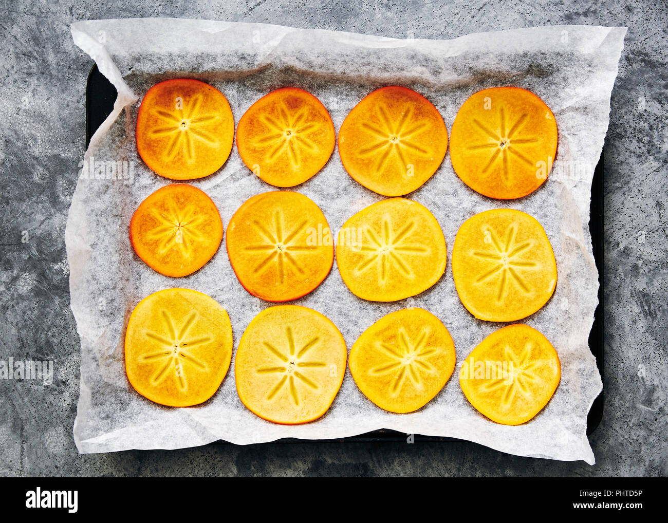 Freshly cut persimmon: bake in the oven to make dried persimmon flowers to decorate a cake. - Stock Image