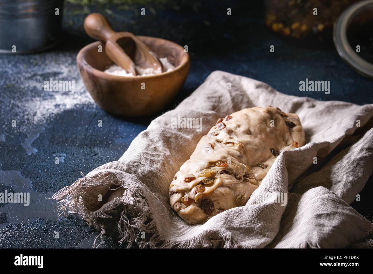 christmas cake traditional german festive baking wholegrain dough stollen preparation on linen napkin with bowls of flour raisins fir tree over da