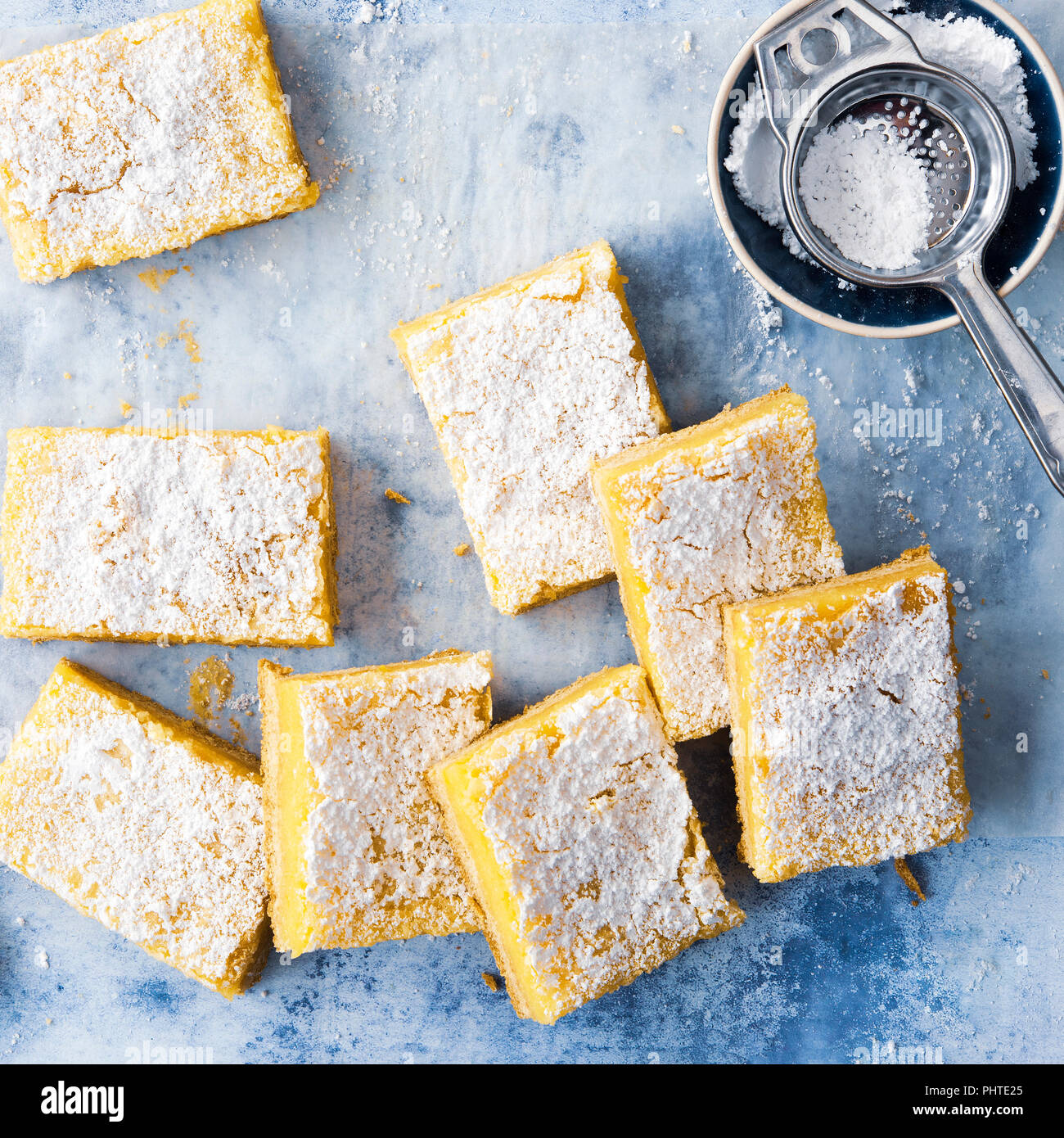 Pieces of homemade lemon slice with icing sugar in a sifter. - Stock Image