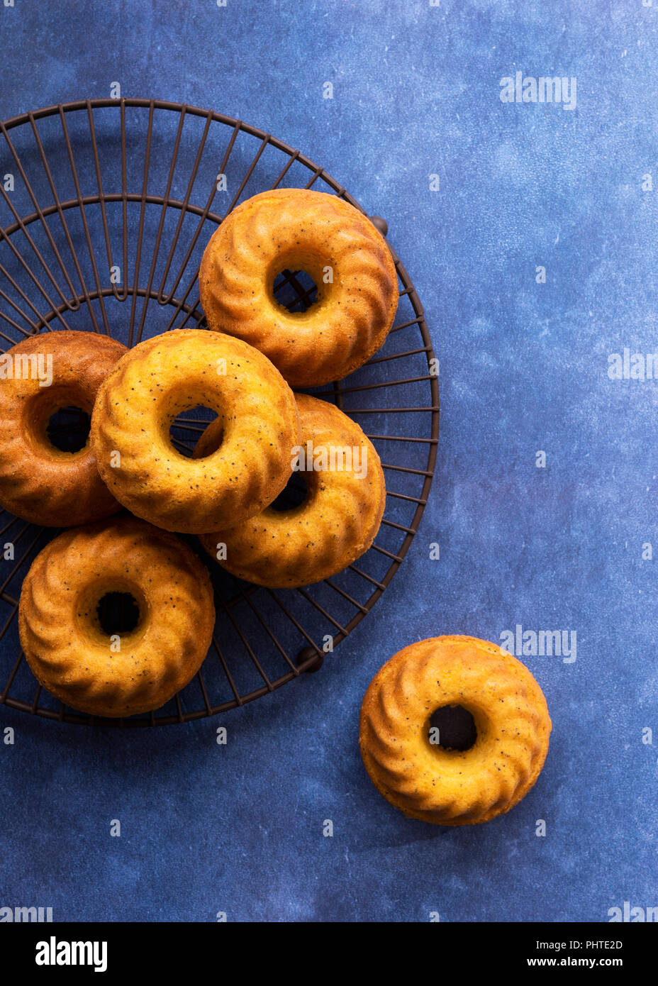 Small orange poppy seed cakes baked in ring tins. - Stock Image