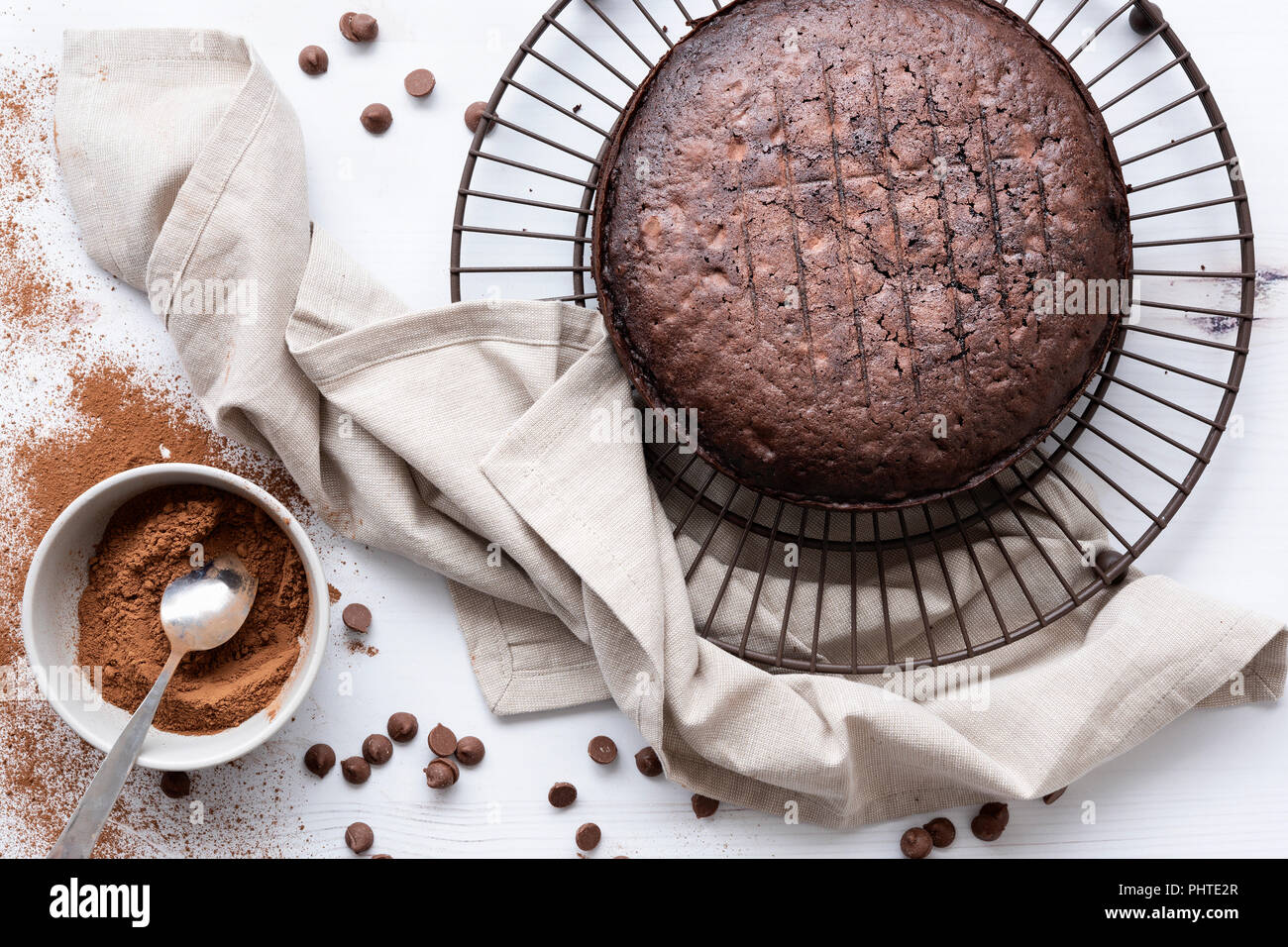 Round home baked chocolate cake cooling on a wire rack. - Stock Image