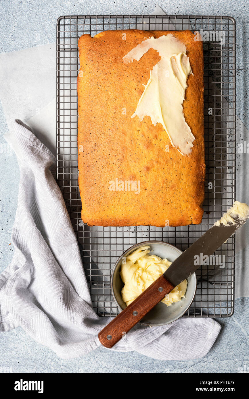 Orange and poppyseed cake partially spread with butter icing. - Stock Image