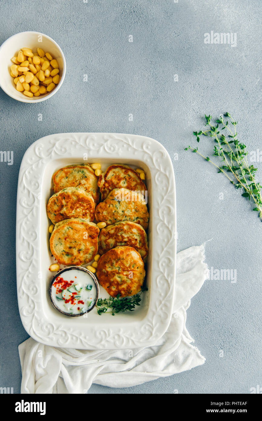 Corn fritters served with yogurt sauce and fresh thyme on the side in a white pan photographed on a grey background from top view. Fresh thyme sprigs  - Stock Image