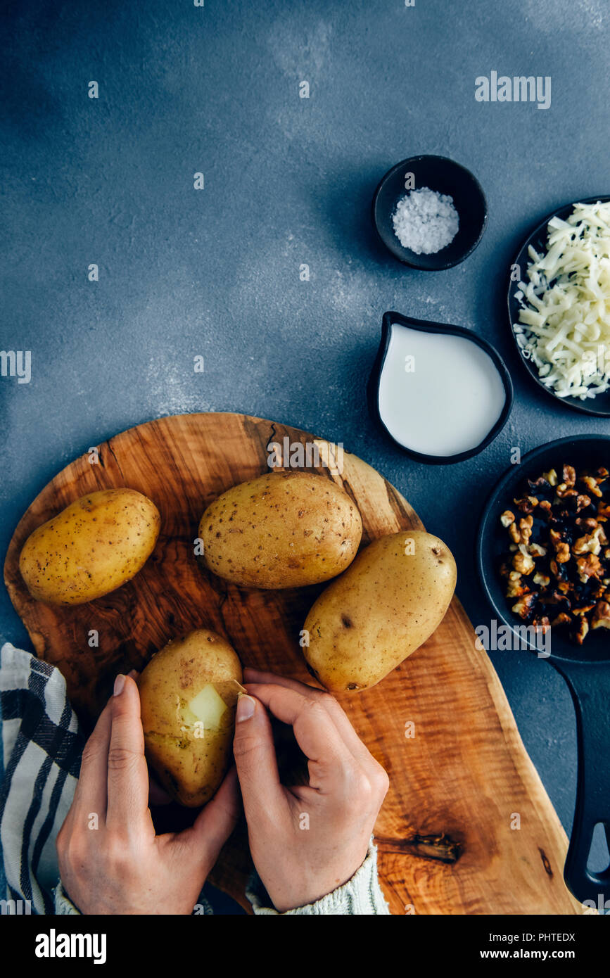 Hands peeling cooked potatoes on a wooden board to make cheesy mashed potatoes photographed from top view. - Stock Image