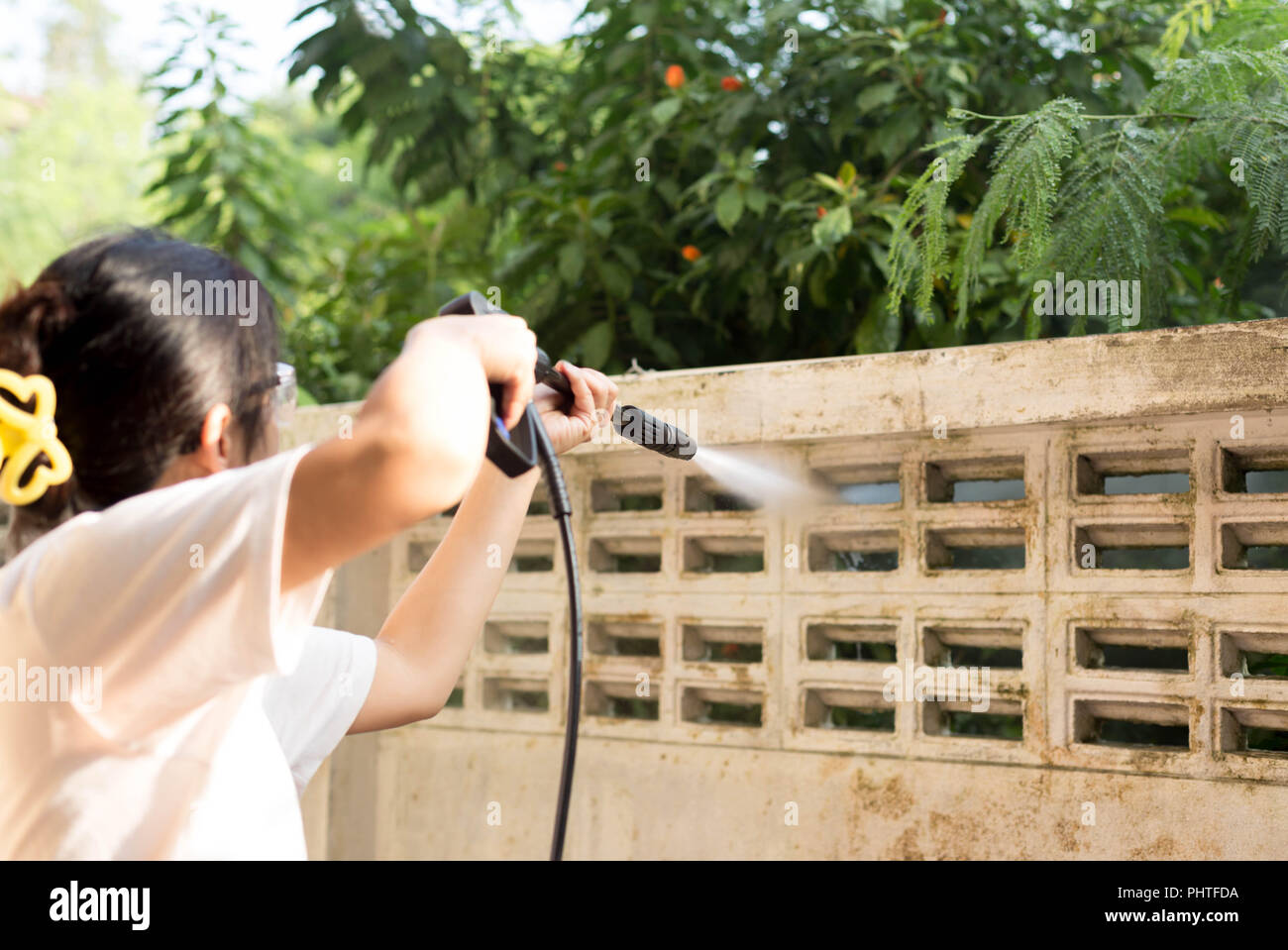 Woman cleaning  waill with high pressure water jet - Stock Image