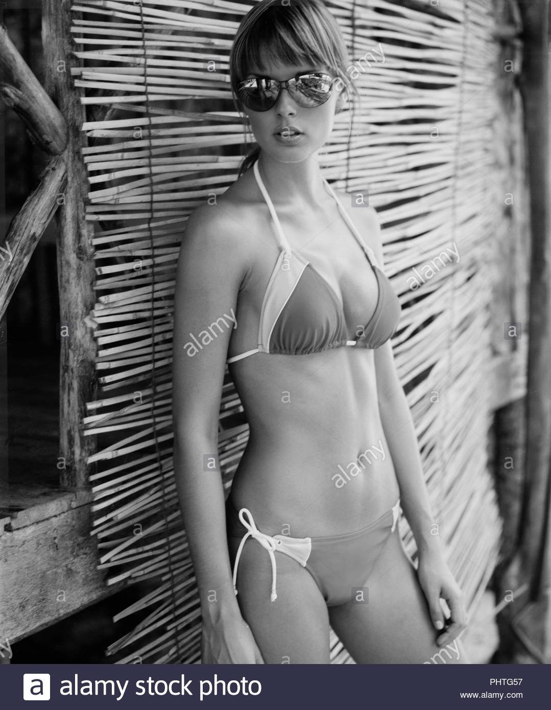 Young woman wearing bikini and sunglasses - Stock Image