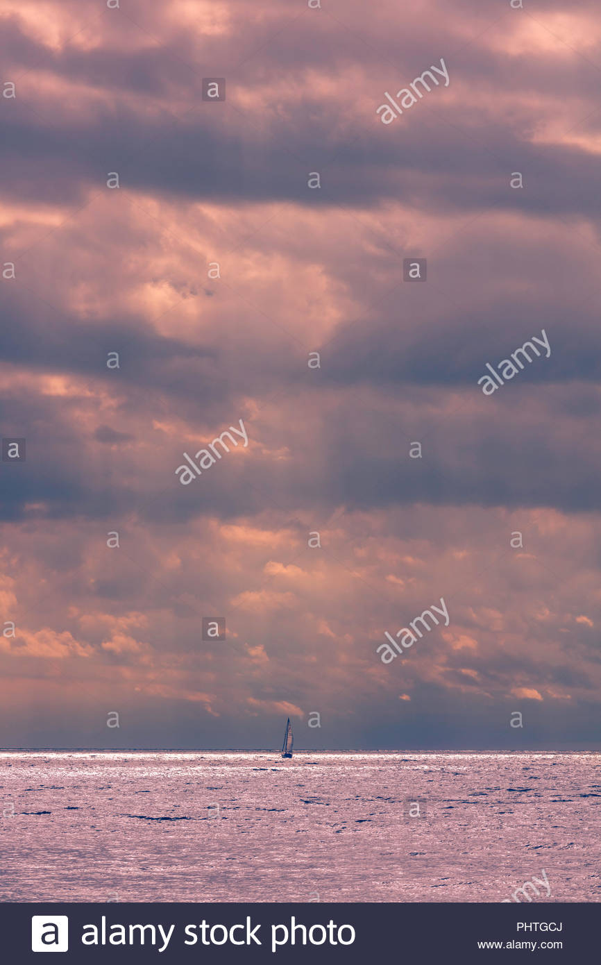 Towering storm clouds on vast Lake Ontario sailboat running before storm near Toronto Ontario Canada - Stock Image