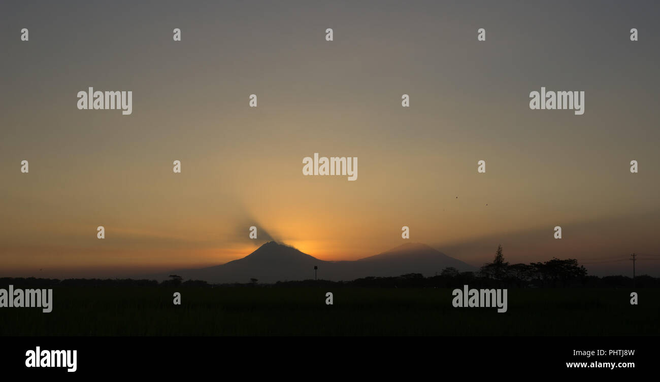 Sunset light between Mount Merapi (left) and Mount Merbabu (right), Central Java, Indonesia - Stock Image