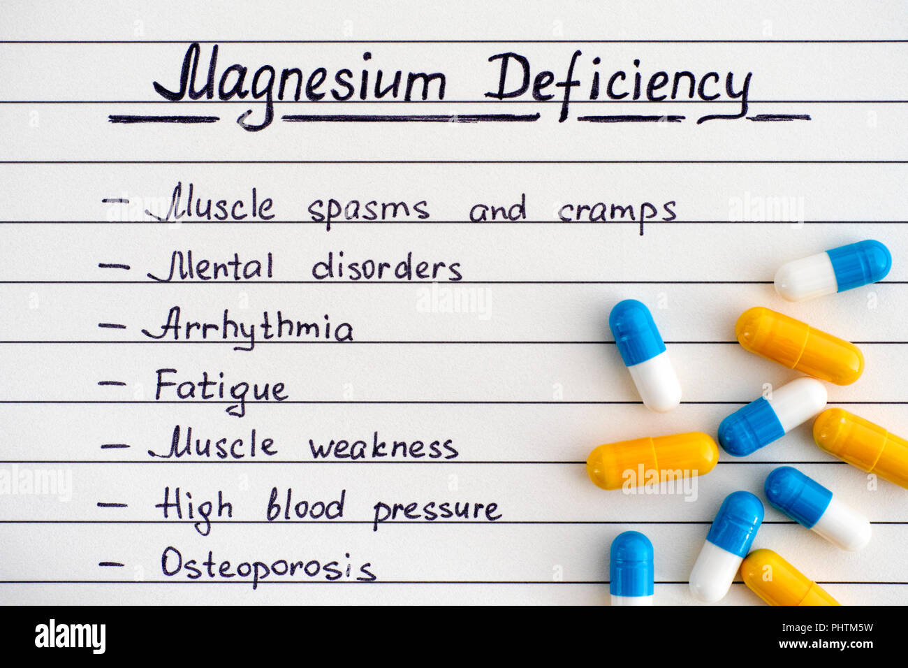 Symptoms of Magnesium Deficiency with some pills. Close-up. - Stock Image
