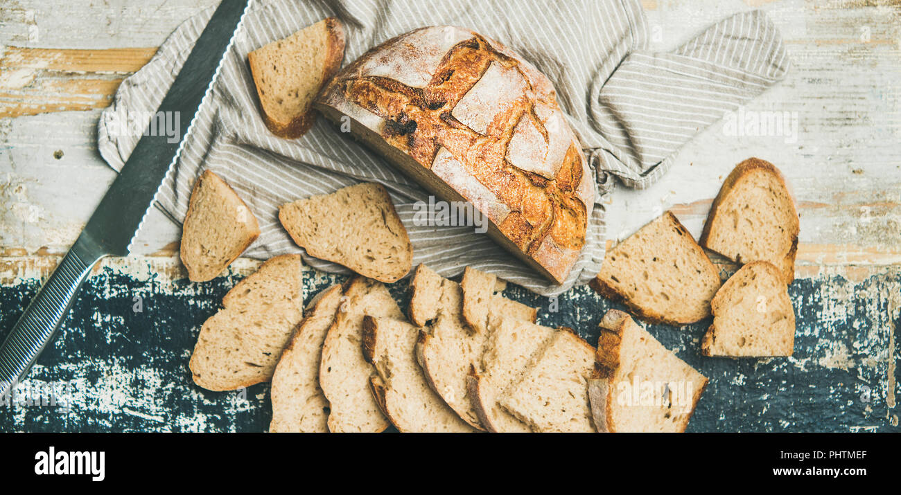 Sourdough wheat bread cut in slices on table, wide composition - Stock Image