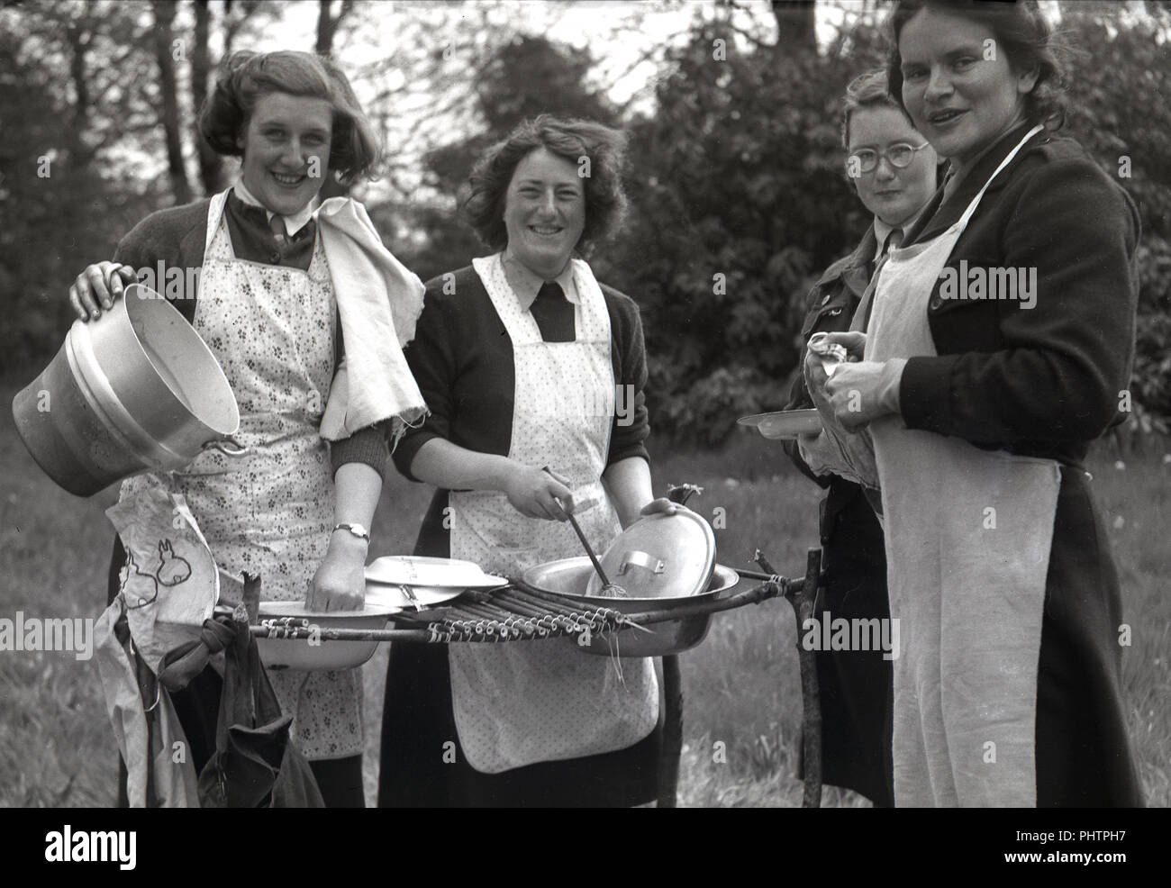 1950s, female adult girl guide leaders or Brown Owls in their aprons doing the washing up on a make-shift top made from sticks, outside at summer camp, England, UK. - Stock Image