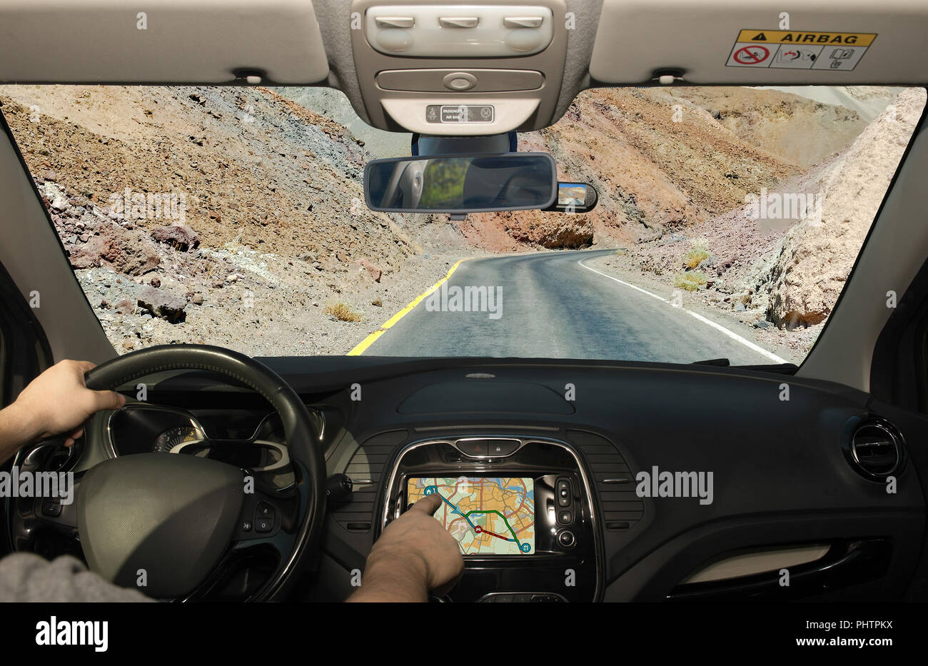 Driving a car while using the touch screen of a GPS navigation system towards a desert road, Death Valley, USA - Stock Image