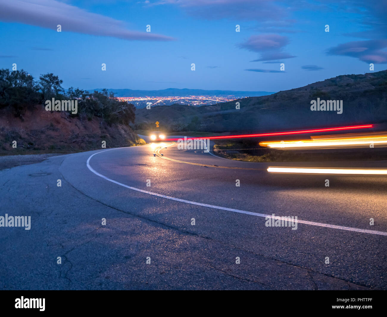 Cars Tail Lights Trails On a Downhill Road With Silicon Valley in the Background - Stock Image