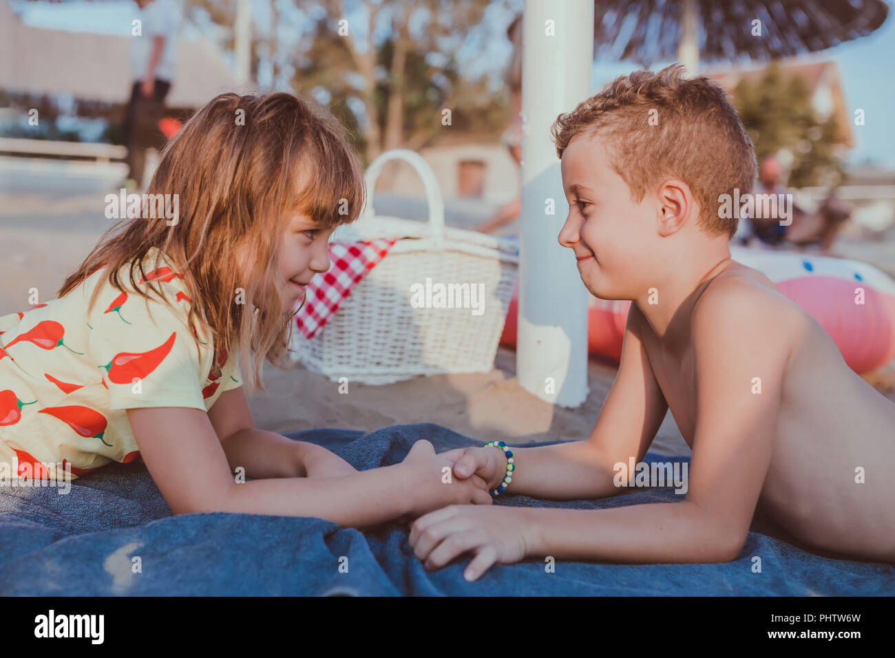 Side View Of A Little Boy And A Girl While Lying On The Beach And
