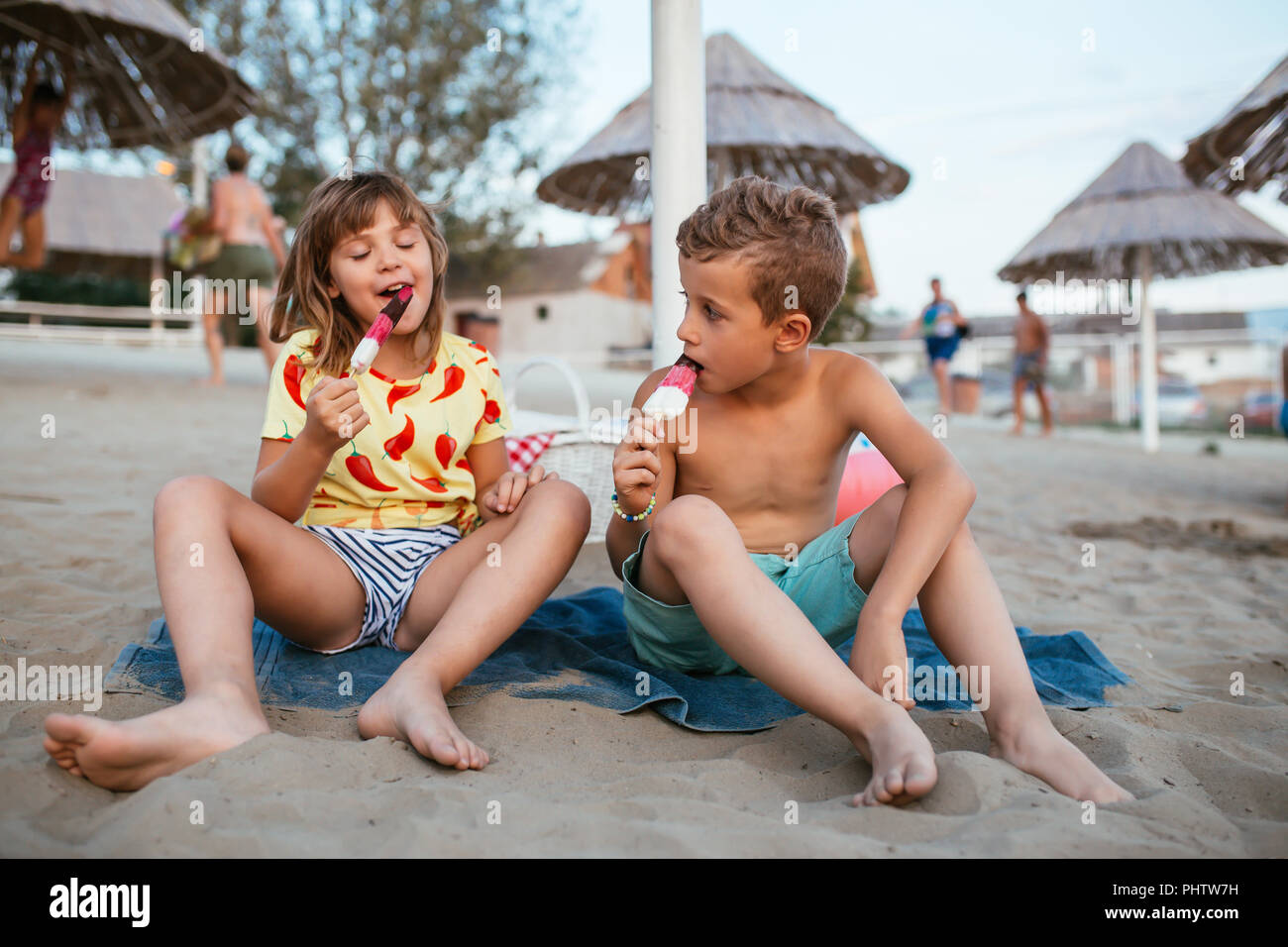 Happy positive children sitting on the sandy beach and eating ice cream. People, children, friends and friendship concept - Stock Image