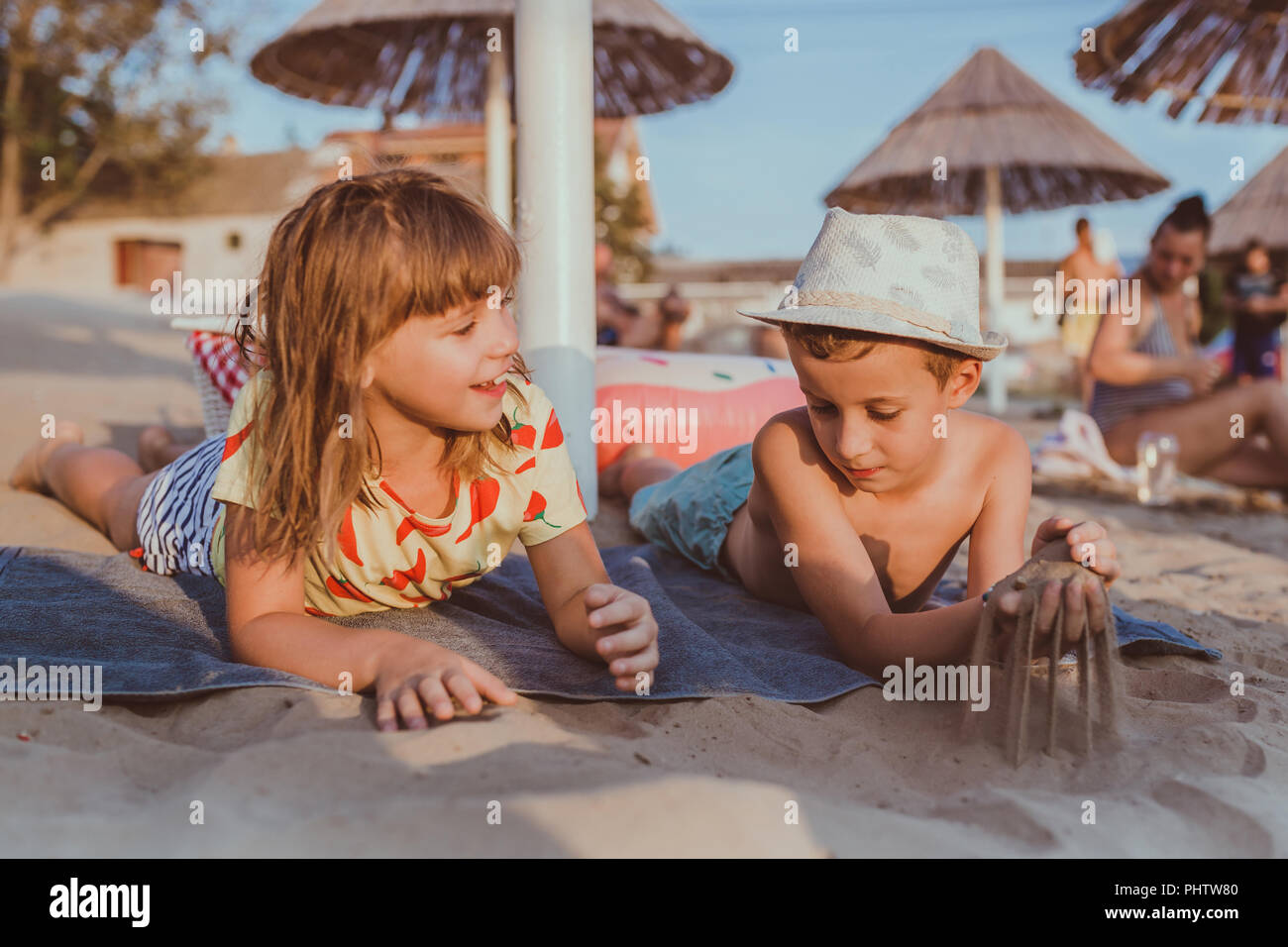 Happy positive children lie on the towel on the beach and playing with sand - Stock Image