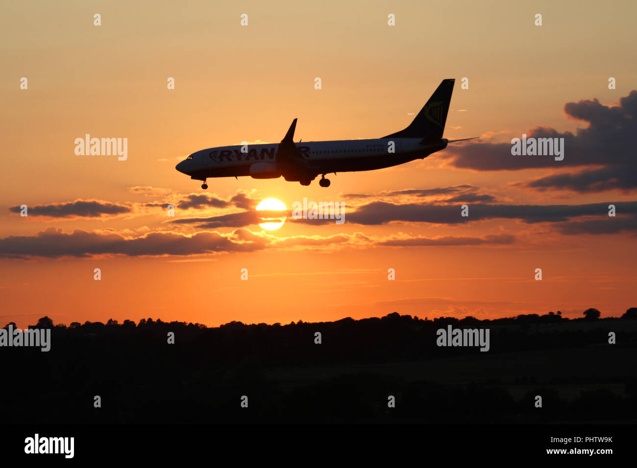 A ryanair boeing 737 jet EI-ESW flies in front of the setting sun as it makes its final approach into Edinburgh airport - Stock Image