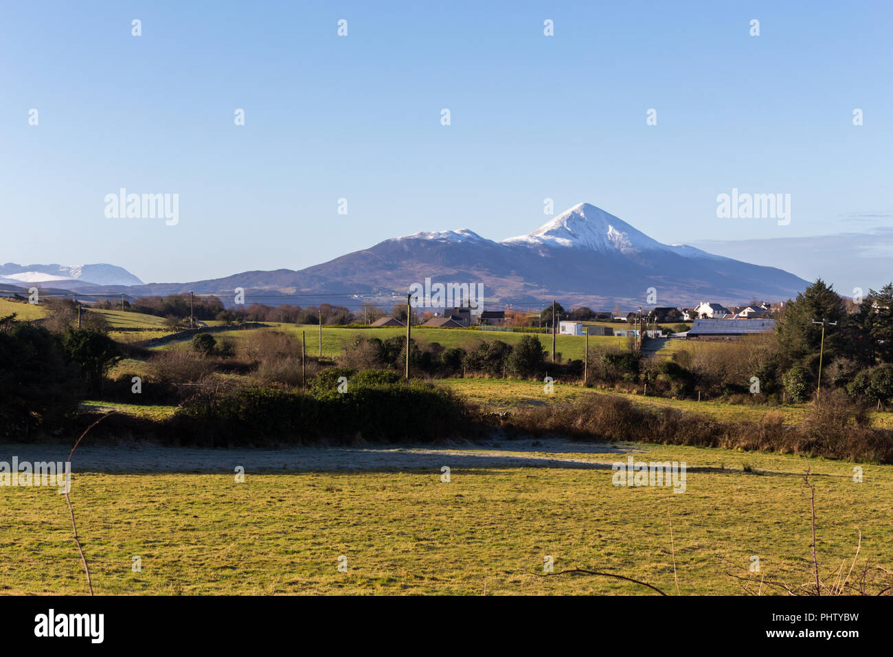 Snowcapped Croagh Patrick, Ireland's Holy Mountain, sen in the distance over green fields. Westport, County Mayo, Ireland. - Stock Image
