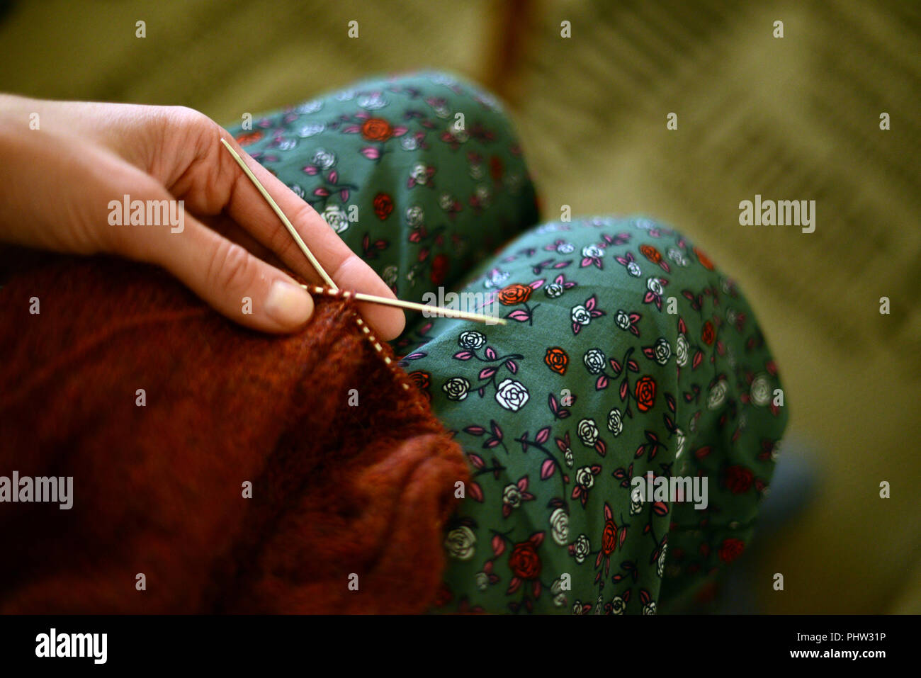 woman holding a knitting needles with knitted handwork in copper color - Stock Image