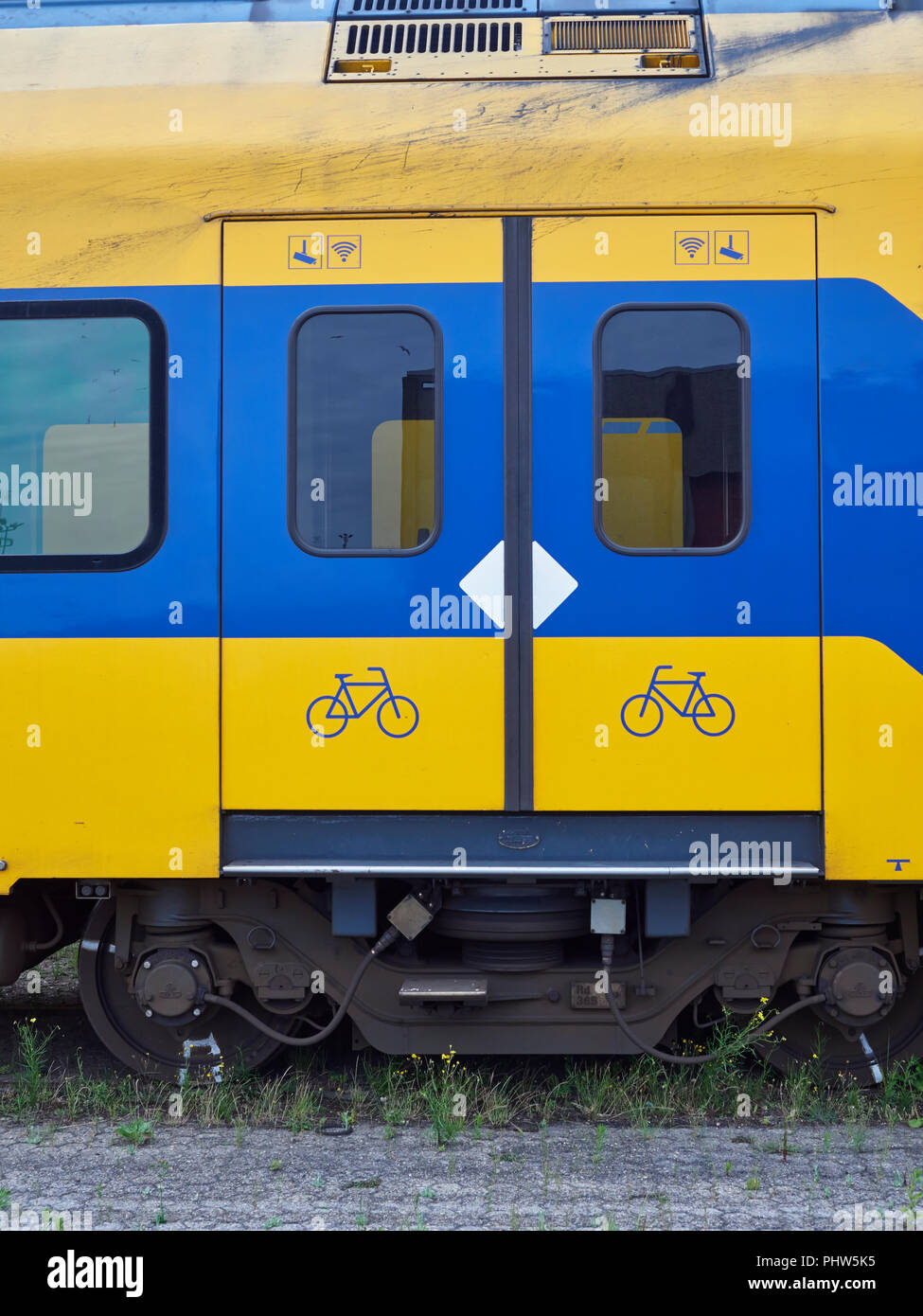 Close up detail of the Sliding Doors and associated Safety Markings on old urban Dutch Railway Passenger Compartments stored at the Container Terminal - Stock Image