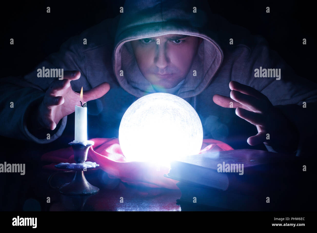Wizard with magic glowing orb and hand holding above a glass of light, candle and candle stick and book on desk. Sorcerer who predicts destiny - Stock Image