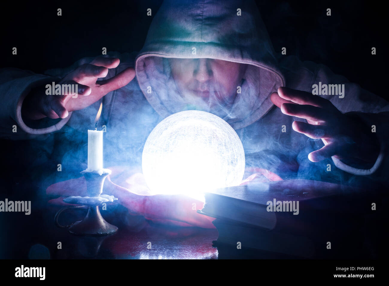 Sorcerer who predicts destiny with glowing magic ball with smoke on desk with candle and old books. Mystic and Halloween concept. Dark and shadow - Stock Image