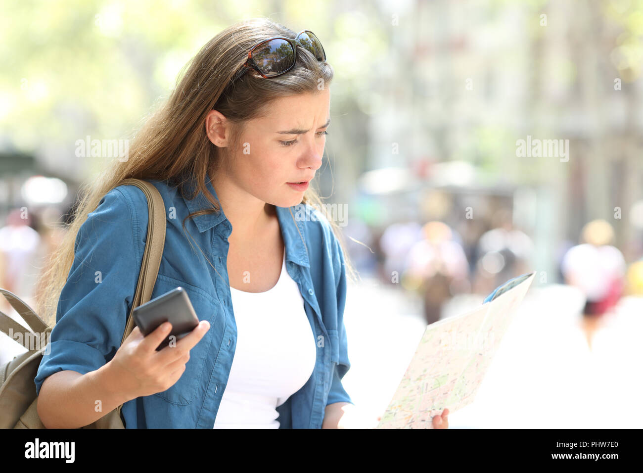 Lost tourist searching direction in a map and a phone in the street - Stock Image
