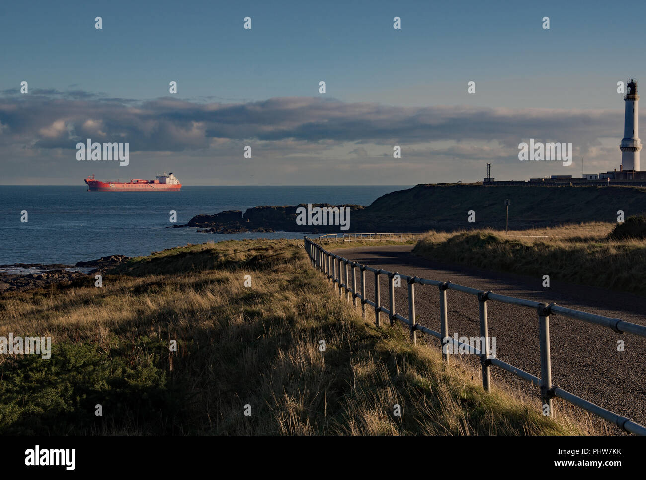 A Stena Teekay ship anchored at the entrance to Aberdeen harbour in Scotland, with the Girdle Ness lighthouse keeping watch. - Stock Image