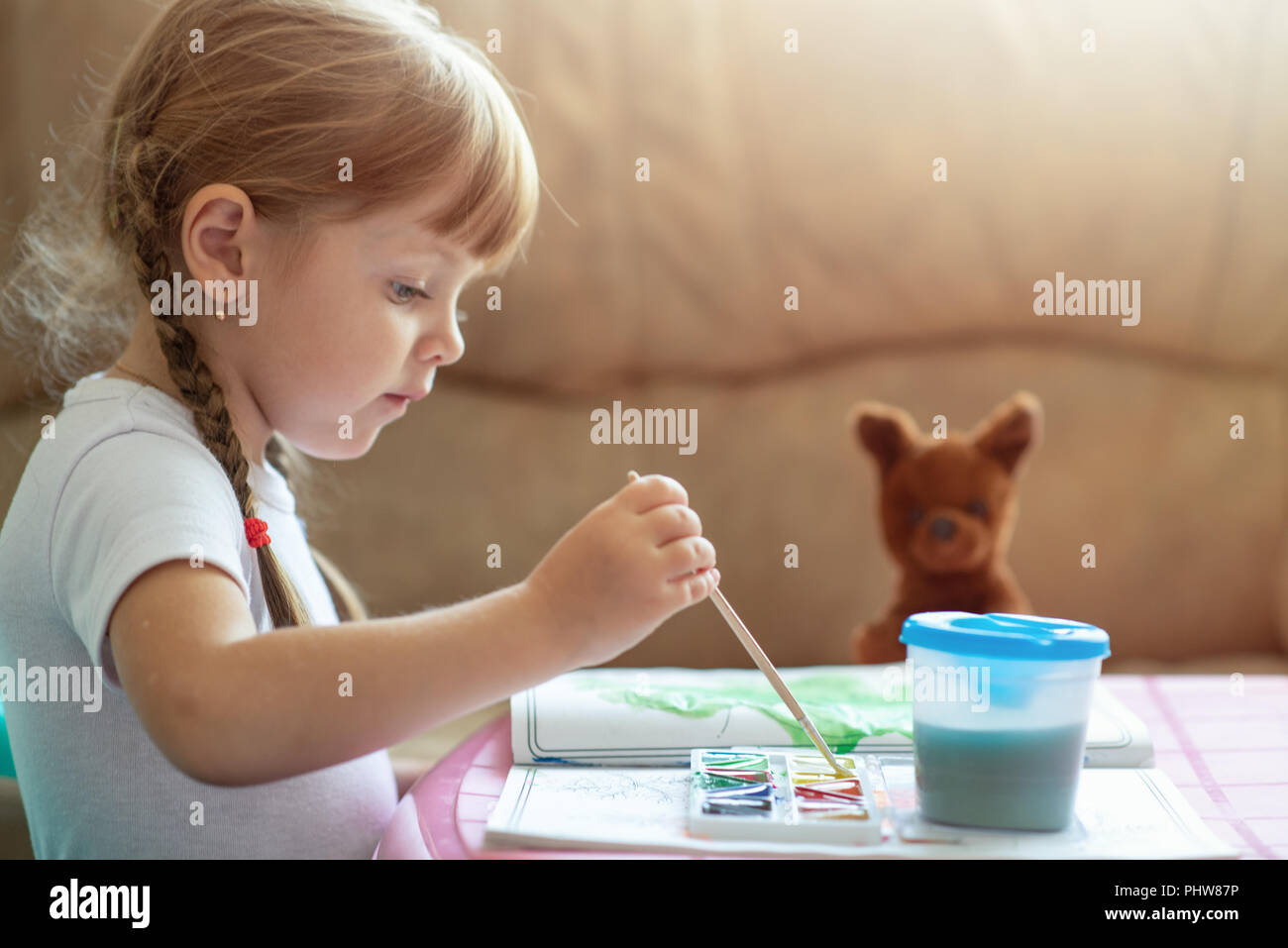 Little four years old caucasian girl coloring image by paint sitting at the table, child development Stock Photo